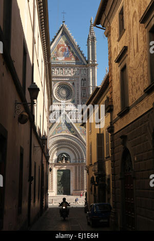 Scooter goes acreoos the narrow street in front of the Orvieto Cathedral (Duomo di Orvieto) in Orvieto, Umbria, - Stock Image