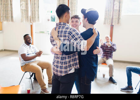 Men hugging in group therapy - Stock Image