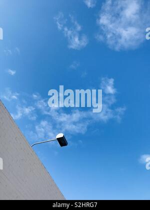 A lamp hangs off a building. - Stock Image