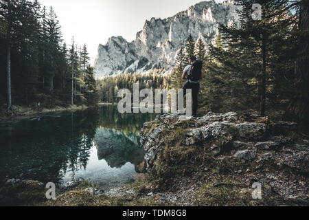 A man hiking to a lake and looking at the reflection of a mountain in austria - Stock Image