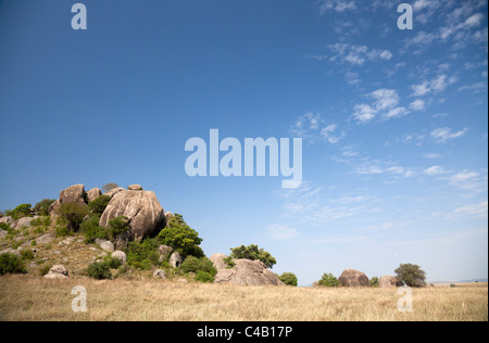 Tanzania, Serengeti. A 4x4 gives an impression of the massive scale of some of Serengeti's kopjes. - Stock Image
