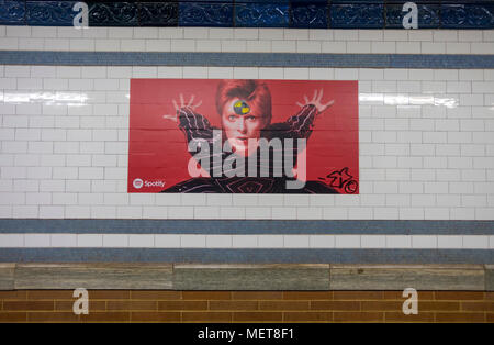 New York, USA. 121 April, 2018. One of many images of David Bowie on the Bleecker Street platform of the he Broadway-Lafayette subway station.  The installation, sponsorsed  by Spotify, is being held in conjunction with the exhibition 'David Bowie IS' at the Brooklyn. The subway installation is just blocks from where the late rock star lived in Soho. The art will be on display until mid May. ©Stacy Walsh Rosenstock - Stock Image