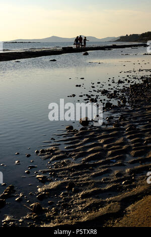 People Enjoying a Sunset Beach Walk, Lagonisi, East Attica, Greece. - Stock Image