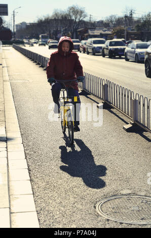 Chinese man rides a yellow rental bicycle in Beijing - Stock Image