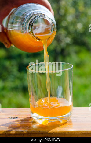 pouring fresh raw unfiltered apple juice into a glass - Stock Image