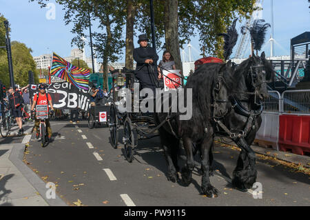 London, UK. 13th October 2018. A funeral procession of cyclists behind a horse-drawn hearse highlights the failure of governments from all the major parties to take comprehensive action on safer cycling. Stop Killing Cyclists call for £3 billion a year to be invested in a national protected cycling network and for urgent action to reduce the toxic air pollution from diesel and petrol vehicles which kills tens of thousands of people every year, and disables hundreds of thousands. The several hundred protesters staged a ten-minute die-in outside Parliament before moving off to a rally in Smith S - Stock Image