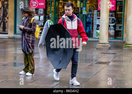 Bath, UK. 8th February, 2019. As storm Eric brings gales and heavy rain across the UK a pedestrian is pictured in the centre of Bath struggling with an umbrella as he braves the heavy rain and wind. Credit: Lynchpics/Alamy Live News - Stock Image