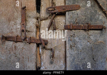 old rusty hinges brackets and clasps on the door of an outbuilding zala county hungary - Stock Image
