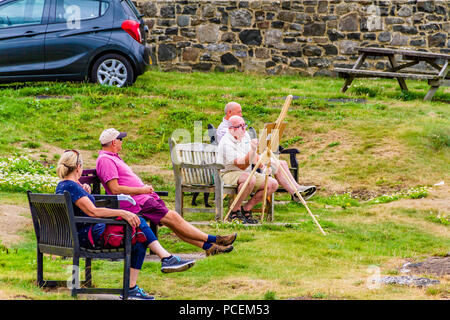 People relax on benches in the northeast village of Craster watching an elderly man paint during the heatwave of August 2018. Craster, Northumberland. - Stock Image