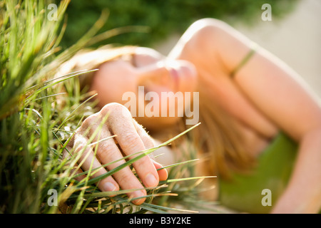 Selective focus portrait of young woman relaxing in grass - Stock Image