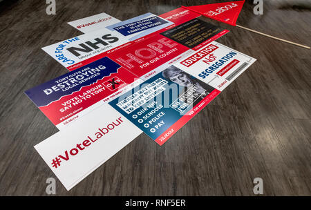 A mosaic of labour Party posters laid on a wooden floor. - Stock Image