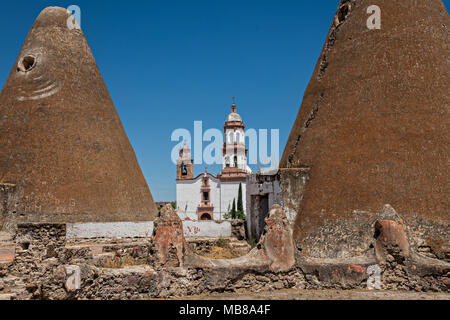 The Iglesia de San Diego De Alcalá church behind the pyramid shaped granaries at the Hacienda de Jaral de Berrio in Jaral de Berrios, Guanajuato, Mexico. The abandoned Jaral de Berrio hacienda was once the largest in Mexico and housed over 6,000 people on the property. - Stock Image