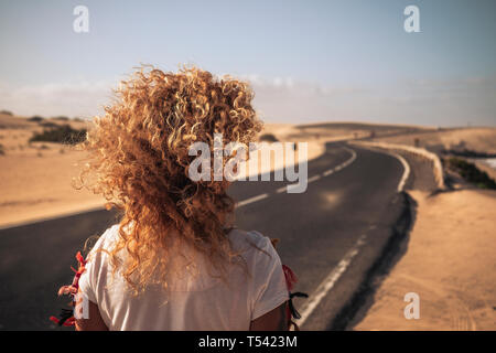 Back view of long blonde curly hair in the wind for freedom independence vacation concept - long asphalt beautiful road with desert dines and beach on - Stock Image
