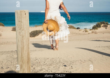 Elegant fashion lady in white dress and natural hat walking to the beach barefoot enjoying the summer holiday vacation day in tropical place - blue se - Stock Image
