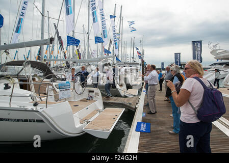 Southampton, UK. 11th September 2015. Southampton Boat Show 2015. Show visitors look on at a row of large yachts - Stock Image