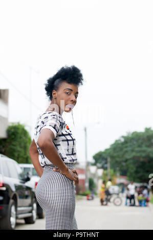 Beautiful african woman like dummy posing in the street, glancing back. - Stock Image