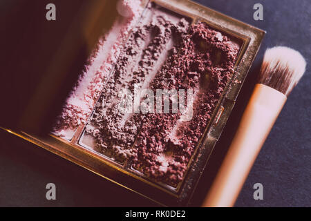 palette with crushed powder eyeshadows in nude and blush tones on dark background with brush, concept of beauty and make-up trends - Stock Image