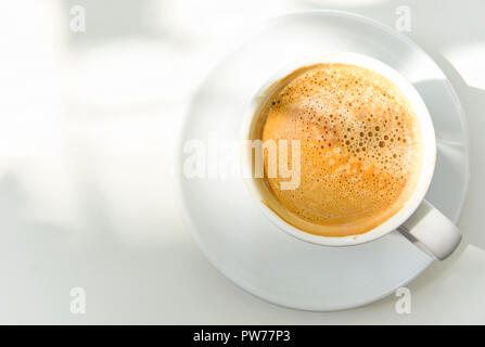 White Cup of Freshly Brewed Coffee on Saucer Table Sunlight Leaks. Top View. Morning Breakfast Energy New Day. Minimalist. Authentic Lifestyle Image C - Stock Image