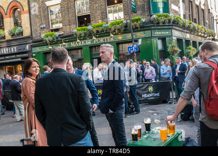 London City Workers after business hours drinking outside in Borough Market London, alfresco meeting lifestyle alcohol drinks culture, spring summer recreation after work lifestyle relaxation de-stress and chilling out - Stock Image