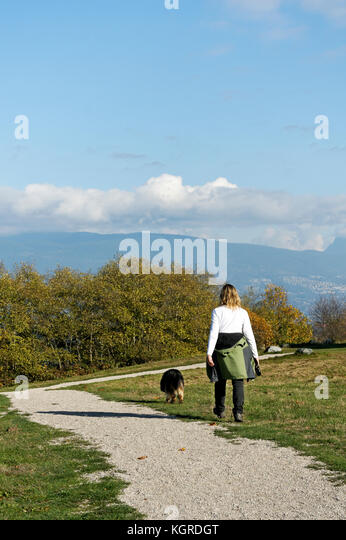 woman-walking-her-dog-along-a-gravel-pat