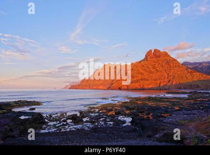 Spanien, Kanarische Inseln, Teneriffa, Punta del Hidalgo, Küste und Anagagebirge während des Sonnenuntergangs. Stockbild