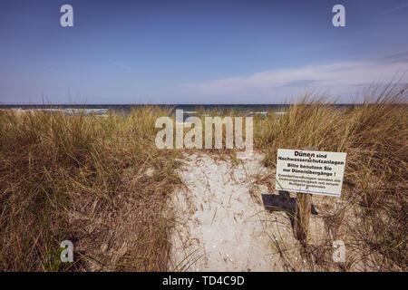 Ein Schild mit einem Warnschild steht an der Düne von der Ostsee Se Stockbild