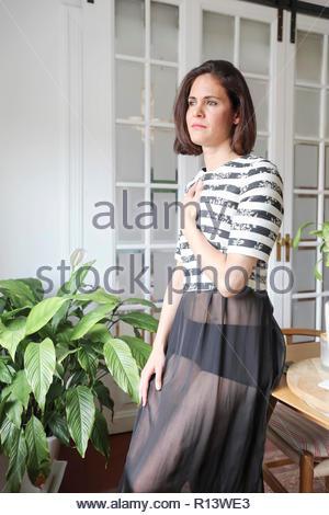 Eine schöne Frau, die von Topfpflanzen Stockbild