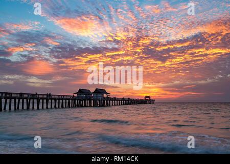 Sonnenuntergang über dem Golf von Mexiko am Naples Pier entlang der Florida Gulf Coast, Naples, Florida, USA Stockbild