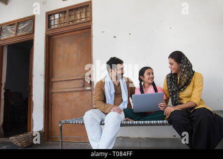 Happy Village Mädchen sitzen mit ihren Eltern auf einem Feldbett mit einem Laptop. Stockbild