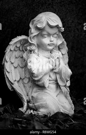 Abbildung eines betenden kleiner Engel als Teil einer Grabstein auf einem Grab Stockbild