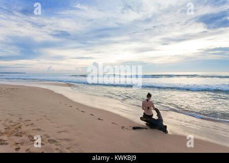Asien - Sri Lanka - induruwa - eine Frau auf einem baumstumpf am Strand sitzen Stockbild