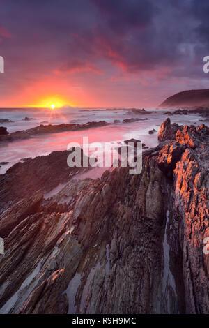 Spektakulären Sonnenuntergang über die felsige Küste von Tsitsikamma-Abschnitt von der Garden Route National Park, Südafrika. Stockbild