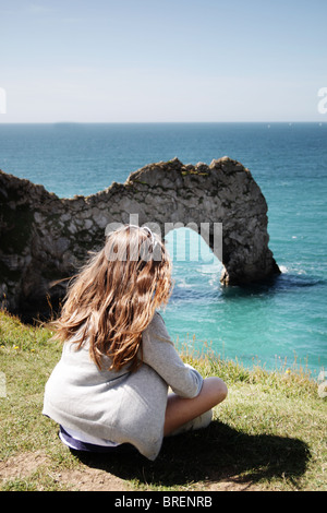 Mädchen saß von Durdle Door, Dorset, England, UK Stockbild