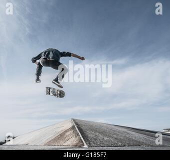 Junger Mann Skateboarden auf Dach Stockbild