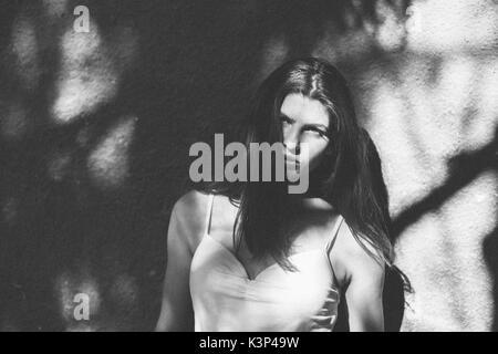 Authentische Frau im Schatten an der Wand Stockbild