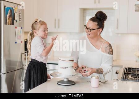 Mutter und Tochter dekorieren Kuchen in der Küche Stockbild