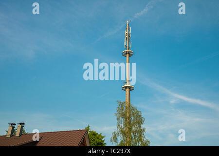 Ein radio Mast für das Mobilfunknetz überragt ein Wohngebäude in den blauen Himmel in einem Wohngebiet. Stockbild