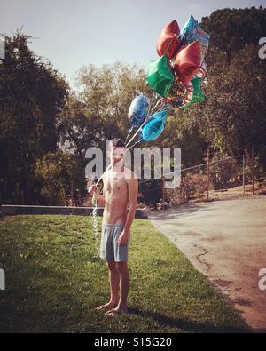 Mann im Hinterhof mit Luftballons Stockbild