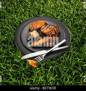 Gegrillte Süßkartoffel mit Sesam auf einer schwarzen Platte und einen Rasen-Hintergrund. Stockbild