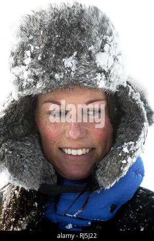 Frau, die in einem verschneiten Pelzkappe Stockbild
