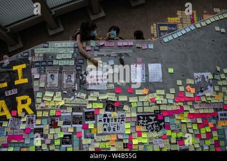 Eine Frau Klebstoffe ein Post-it mit Nachrichten gegen die Auslieferung Bill und pro-Demokratie in einem Lennon Wand im gesetzgebenden Rat Gebäude. Hong Kong Demonstranten versammelten für ein weiteres Wochenende der Proteste gegen die umstrittene Auslieferung Rechnung und mit einer wachsenden Liste von Beschwerden, die der Aufrechterhaltung des Drucks auf Chief Executive Carrie Lam. Stockbild