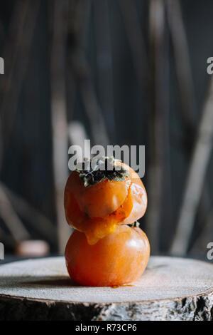Kaki Frucht auf ein anderes auf rustikalen Schneidebrett Stockbild