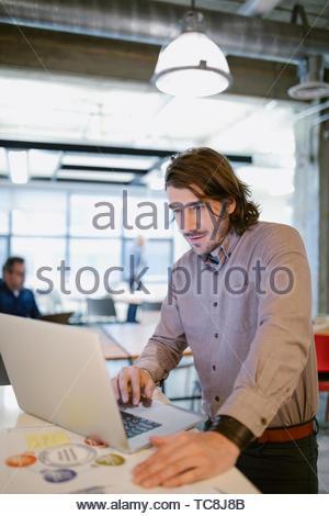 Fokussierte Geschäftsmann mit Laptop im Büro Stockbild