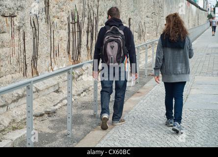 Touristen zu Fuß entlang eines erhaltenen Abschnitts der Berliner Mauer an der Topographie des Terrors-Freilichtmuseum Stockbild