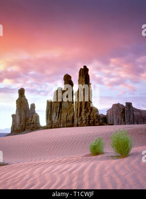 Sanddüne und Totempfahl Felsformation bei Sonnenaufgang. Monument Valley, Arizona Stockbild