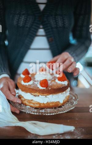Frau mit einem schönen Kuchen gebacken. Stockbild