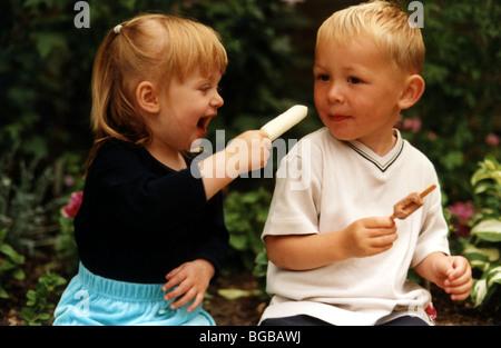 Foto von Spielkameraden Bruder Schwester Familie Lolly pop teilen Stockbild