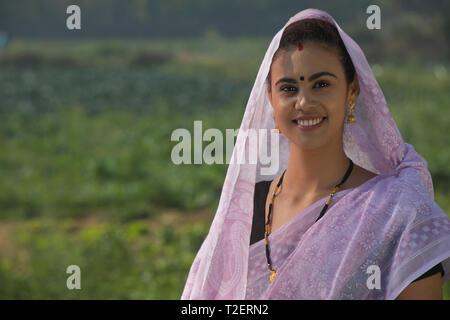 Porträt einer Frau, die in einem landwirtschaftlichen Gebiet mit dem Kopf unter die Sari. Stockbild