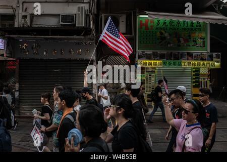Demonstranten mit einer amerikanischen Flagge März während der bürgerlichen Menschenrechte vor März. Hongkong Demonstranten versammelten für ein weiteres Wochenende der Proteste gegen die umstrittene Auslieferung Rechnung und mit einer wachsenden Liste von Beschwerden, die der Aufrechterhaltung des Drucks auf Chief Executive Carrie Lam. Stockbild