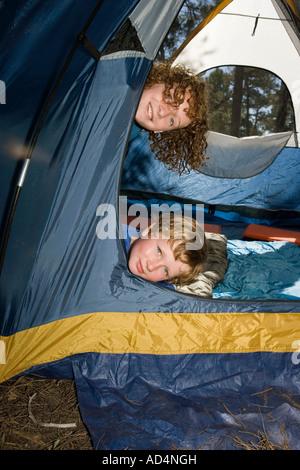 Zwei Jungen aus einem Zelt spähen Stockbild